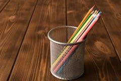 Ajuste dos lápis coloridos em um copo do metal em uma tabela de madeira fotografia de stock