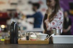 Ajuste dos pratos e dos acessórios para a preparação do café filtrado marcado na barra no fundo borrado com imagens de stock royalty free