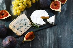 Ajuste dos queijos diferentes em um fundo rústico de madeira Placa de queijo na tabela  imagens de stock royalty free