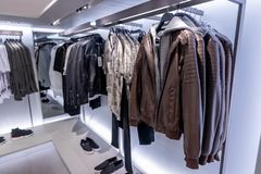 Ajuste dos revestimentos dos homens na loja elevadores, vidro e metal Loja do revestimento garment imagem de stock royalty free