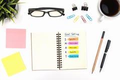 Ajuste esperto do objetivo com material de escritório sobre a mesa branca Fotografia de Stock Royalty Free