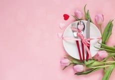 Ajuste festivo da tabela com cutelaria, as tulipas rosados e os corações no pi Fotos de Stock Royalty Free
