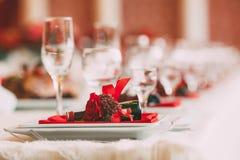 Ajuste festivo de la tabla de la boda Platos adornados con una flor roja y los accesorios para la celebración ilustraciones Fotografía de archivo