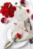 Ajuste festivo de la tabla con las rosas rojas Foto de archivo libre de regalías