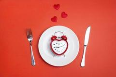 Ajuste festivo de la tabla con los cubiertos y el despertador en forma de corazón Imágenes de archivo libres de regalías