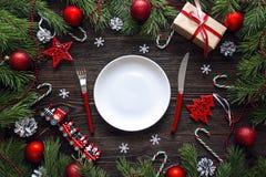Ajuste festivo de la tabla con los cubiertos y las decoraciones de la Navidad encendido Imagen de archivo