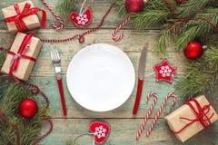 Ajuste festivo de la tabla con los cubiertos y las decoraciones de la Navidad encendido Imagen de archivo libre de regalías