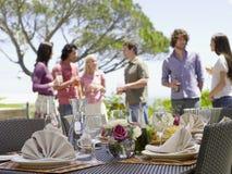 Ajuste fino de la mesa de comedor con los amigos en fondo Imagenes de archivo