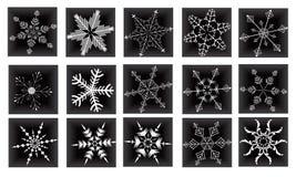Ajuste flocos de neve festivos em um fundo preto Foto de Stock
