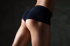 Ajuste hermoso, cuerpo femenino atractivo en gris oscuro Fotos de archivo libres de regalías
