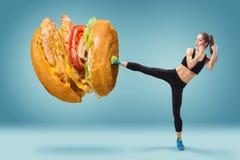 Ajuste, jovem, Hamburger energético do encaixotamento da mulher como o alimento insalubre imagens de stock