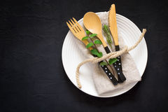 Ajuste natural da tabela com a forquilha de bambu da faca e colher em um blac imagem de stock