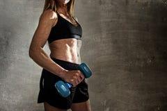 Ajuste anônimo e mulher forte do esporte que mantêm o peso no seu levantamento da mão desafiante na atitude fresca Foto de Stock Royalty Free
