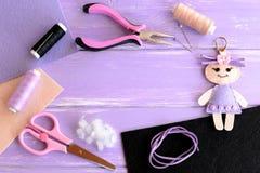 Ajuste para a atividade e a faculdade criadora das crianças A boneca de feltro, tesouras, linha, agulhas, pinos, alicates, cabo d imagem de stock