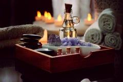 Ajuste para procedimentos dos termas das pedras para a massagem, óleo, sal do mar de mentiras da violeta em uma caixa de madeira  Foto de Stock Royalty Free