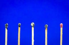 Ajuste queimado do fósforo no fundo azul para ideias e inspiratio Fotos de Stock Royalty Free