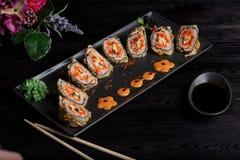 Ajuste rolos de sushi em uma placa retangular preta em um fundo escuro imagem de stock