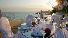 Ajuste romántico de la tabla en el embarcadero en la puesta del sol Imagenes de archivo
