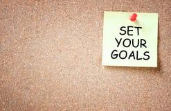 Ajuste seu conceito dos objetivos. pegajoso fixado ao corkboard com sala para o texto. Imagens de Stock Royalty Free