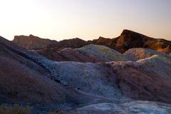 Ajuste Sun nos cumes corroídos coloridos das montanhas, formações de rocha antigas do lugar o mais quente na terra, o Vale da Mor foto de stock