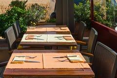Ajuste tabelas no espaço para refeições exterior Imagem de Stock