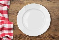 Ajuste vazio branco da placa de jantar na tabela de madeira Imagens de Stock Royalty Free