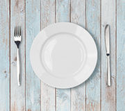 Ajuste vazio branco da placa de jantar na tabela de madeira azul imagens de stock