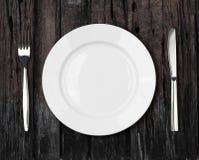 Ajuste vazio branco da placa de jantar na tabela de madeira escura velha Imagem de Stock Royalty Free