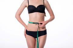 Ajuste y señora joven sana que miden su cintura con una cinta métrica en centímetros y milímetros Ella tiene su gimnasio negro Foto de archivo libre de regalías