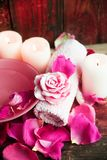 Ajustes del balneario con las rosas Rosas frescas y pétalos color de rosa en un cuenco de agua y de diversos artículos usados en  Imágenes de archivo libres de regalías
