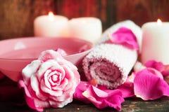 Ajustes del balneario con las rosas Rosas frescas y pétalos color de rosa en un cuenco de agua y de diversos artículos usados en  Foto de archivo libre de regalías