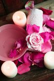 Ajustes del balneario con las rosas Rosas frescas y pétalos color de rosa en un cuenco de agua y de diversos artículos usados en  Foto de archivo