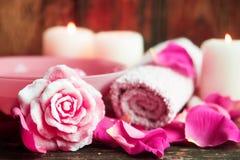 Ajustes del balneario con las rosas Rosas frescas y pétalos color de rosa en un cuenco de agua y de diversos artículos usados en  Imagen de archivo libre de regalías