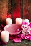 Ajustes del balneario con las rosas Rosas frescas y pétalos color de rosa en un cuenco de agua y de diversos artículos usados en  Fotos de archivo libres de regalías