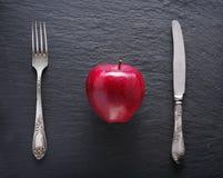 Ajustes rojos de la manzana y de la tabla en un fondo oscuro Imagenes de archivo