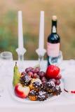 Ajustes románticos al aire libre de la tabla de cena con el vino, los vidrios, los dulces y las velas Fotografía de archivo