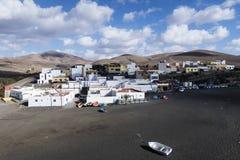 Ajuy村庄在费埃特文图拉岛的有反对山脉和部分地被覆盖的蓝天的黑暗的沙子海滩的 免版税库存图片