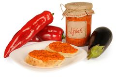 Ajvar - delicious dish of red and green peppers, onions, garlic, eggplant. Ajvar in jar. Sauce spread on two slices of bread on pl Stock Photo