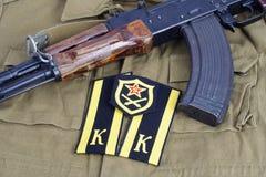 AK47 с меткой плеча кадета Советской Армии и заплатой плеча артиллерии Советской Армии на хаки форме Стоковые Фотографии RF