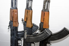 AK-47 assault rifles close up. Close up three Soviet made AK-47 assault rifles leaning on white wall Stock Images
