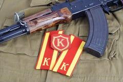 AK 47 avec la correction soviétique de marque d'épaule de cadet d'armée et d'épaule de commandant sur le fond uniforme kaki Photos stock