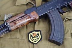 AK 47 mit sowjetischem Pionierwesen-Schulterflecken der Armee auf kakifarbigem einheitlichem Hintergrund Stockfotos