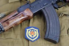 AK 47 mit sowjetischem Schulterflecken der mechanisierten Infanterie der Armee auf kakifarbigem einheitlichem Hintergrund Lizenzfreie Stockfotografie