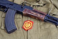 AK 47 mit sowjetischem Schulterflecken der mechanisierten Infanterie der Armee auf kakifarbigem einheitlichem Hintergrund Lizenzfreie Stockbilder