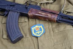 AK 47 with Soviet Army Air Force shoulder patch on khaki uniform background Royalty Free Stock Photo
