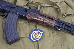 AK47 with Soviet Army Mechanized infantry shoulder patch on khaki uniform. Background Stock Photos