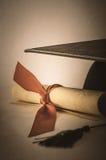 Akademikermössa- och diplomsnirkel som binds med bandet med tappningEff arkivbilder