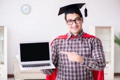 Akademikermössan och innehavet för student för toppen hjälte den bärande en bärbar dator Arkivbilder