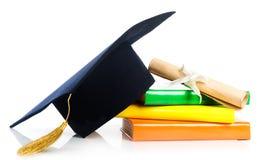 Akademikermössa- och tappningavläggandet av examen bläddrar, bundet med det röda bandet Arkivbild