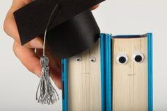 Akademisk hatt på boken Ledsna och lyckliga sinnesrörelser arkivfoton